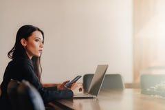 Молодая привлекательная эмоциональная девушка в одеждах дел-стиля сидя на столе на ноутбуке и телефоне в офисе или аудитории стоковая фотография
