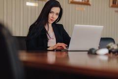 Молодая привлекательная эмоциональная девушка в одеждах дел-стиля сидя на столе на ноутбуке и телефоне в офисе или аудитории стоковое изображение