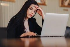 Молодая привлекательная эмоциональная девушка в одеждах дел-стиля сидя на столе на ноутбуке и телефоне в офисе или аудитории стоковое фото rf