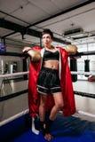 Молодая приятная женщина боксера в оборудовании бокса стоя на кольце Стоковые Изображения RF