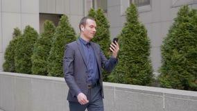Молодая прогулка бизнесмена с беспроводными наушниками в его ушах и говорить на видео- звонке на смартфоне