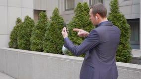 Молодая прогулка бизнесмена с беспроводными наушниками и агрессивно водит обсуждение на видео- звонке на смартфоне сток-видео