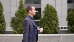 Молодая прогулка и руководства бизнесмена деловая беседа на беспроводных наушниках в его ушах