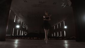 Молодая профессиональная балерина делая круговые движения на этапе Красивые танцы девушки в фарах в вечере во время акции видеоматериалы