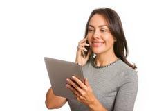 Молодая профессиональная женщина используя планшет и говорить на ее изолированном мобильном телефоне стоковая фотография rf