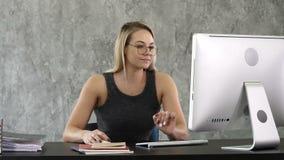 Молодая профессиональная женщина сидя вниз на столе и работая с компьютером сток-видео