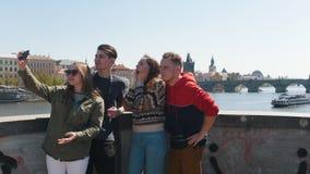 Молодая путешествуя группа в составе друзья стоя на мосте и принимая selfie акции видеоматериалы