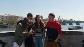 Молодая путешествуя группа в составе друзья стоя на мосте принимая selfie и смотря его сток-видео