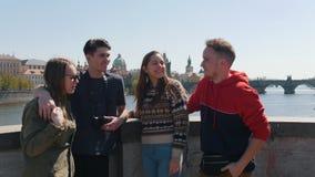 Молодая путешествуя группа в составе друзья стоя на мосте сток-видео