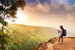 Молодая путешествуя женщина с шляпой рюкзака и камера стоят на верхней части красивого вида скалы горы наблюдая древесин и неба стоковые фото