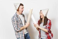 Молодая раздражанная женщина, человек в случайных одеждах держа крены обоев и враждуя белизна изолированная парами стоковое изображение rf