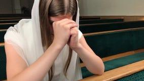 Молодая религиозная посвященная женщина моля в баптистской церкви Верный католик на европейском соборе: внутренность святого мест акции видеоматериалы