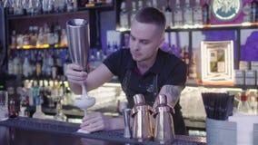 Молодая решетка бармена небольшой киви на терке над стеклом сметанообразного положения коктейля на счетчике бара Длинная полка сток-видео