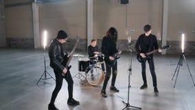 Молодая рок-группа имея повторение в ангаре Члены группы нося черные одежды стоковая фотография rf