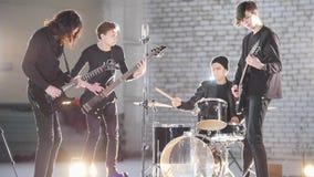 Молодая рок-группа имея повторение в гараже Члены группы нося черные одежды Яркое освещение стоковое фото