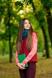 Молодая романтичная девушка читая книгу сидя на траве Стоковое Изображение