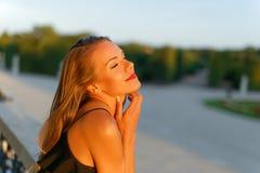 Молодая романтичная женщина мечтая с закрытыми глазами в заходе солнца Стоковое фото RF