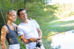 Молодая рыбная ловля пар на пруде банков Стоковые Фото