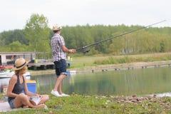 Молодая рыбная ловля пар на пруде банков Стоковое Изображение RF