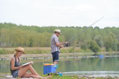 Молодая рыбная ловля пар на пруде банков Стоковая Фотография