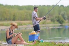 Молодая рыбная ловля пар на пруде банков Стоковая Фотография RF
