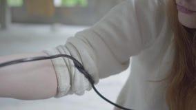 Молодая рыжеволосая девушка наркомана связывает шнур на ее руке для спешкы крови к вене для того чтобы принять другую дозу лекарс видеоматериал