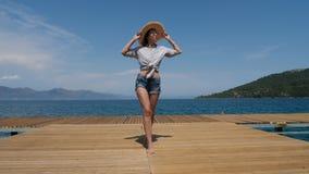 Молодая сексуальная девушка в шляпе и шортах идя на пристань сток-видео