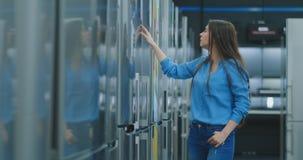 Молодая сексуальная женщина брюнета в рубашке для открытия двери холодильника в магазине приборов и, который нужно сравнить с дру видеоматериал