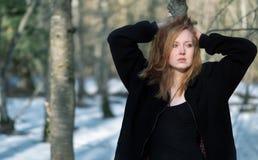 Молодая сексуальная женщина в черных одеждах, с красными волосами, выглядя грустный, в лесе зимы стоковые фотографии rf