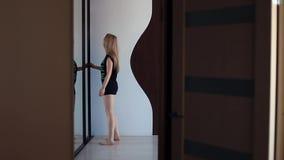 Молодая сексуальная женщина идет к ящику в комнате квартиры живущей, выбирает вверх одевает акции видеоматериалы