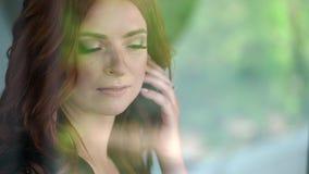 Молодая сексуальная женщина красно-волос в черном женском белье смотря окно акции видеоматериалы