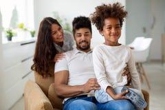 Молодая семья быть шаловливый дома Стоковая Фотография