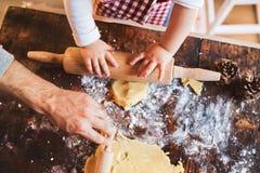 Молодая семья делая печенья дома Стоковая Фотография RF