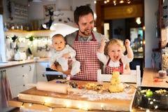 Молодая семья делая печенья дома Стоковые Изображения RF