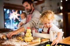 Молодая семья делая печенья дома Стоковые Изображения