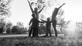 Молодая семья играя с листьями осени в monochrome greyscal стоковая фотография