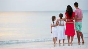 Молодая семья из четырех человек на каникулах пляжа на заходе солнца акции видеоматериалы