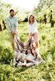 Молодая семья имея потеху в яблоневом саде стоковое фото