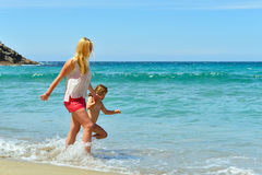 Молодая семья имея потеху на пляже Стоковая Фотография RF