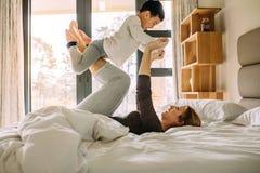Молодая семья имея потеху пока играющ на кровати стоковое изображение rf