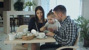 Молодая семья используя компьтер-книжку, беседуя и усмехаясь в кафе или ресторане Стоковые Изображения