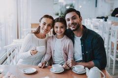Молодая семья отдыхает в кафе стоковое изображение rf