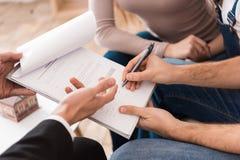 Молодая семья подписывает согласование бизнес-партнера купить дом вместе с риэлтором Стоковые Фотографии RF