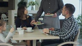 Молодая семья принимает еду в кафе или ресторане Кельнер совершает ошибка и смущает блюда Смотреть отца и матери стоковое изображение