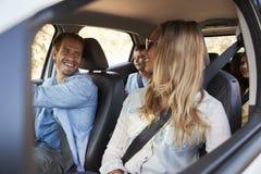 Молодая семья при 2 дет идя на праздник в автомобиле Стоковое Фото