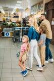молодая семья при 2 дет ходя по магазинам совместно Стоковые Изображения
