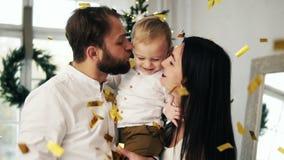 Молодая семья при их милый маленький малыш быть при сверкная confetti падая совсем вокруг праздновать видеоматериал