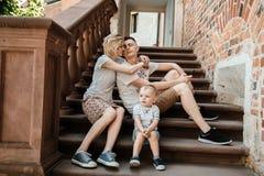 Молодая семья Родители сидят с их сыном на лестницах Мама и папа и ваш младенец мальчик немногая стоковые фотографии rf