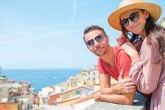 Молодая семья 2 с большим взглядом на старой деревне Riomaggiore в медовом месяце, Cinque Terre, Лигурии, Италии европейско стоковое изображение
