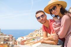 Молодая семья 2 с большим взглядом на старой деревне Riomaggiore в медовом месяце, Cinque Terre, Лигурии, Италии европейско стоковая фотография rf